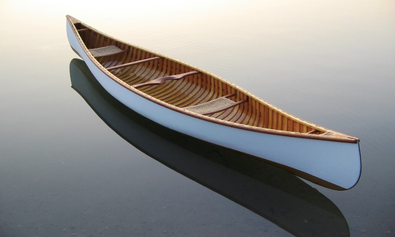 Algonquin Canoe rests in the water - White Canvas and Shellac finnish